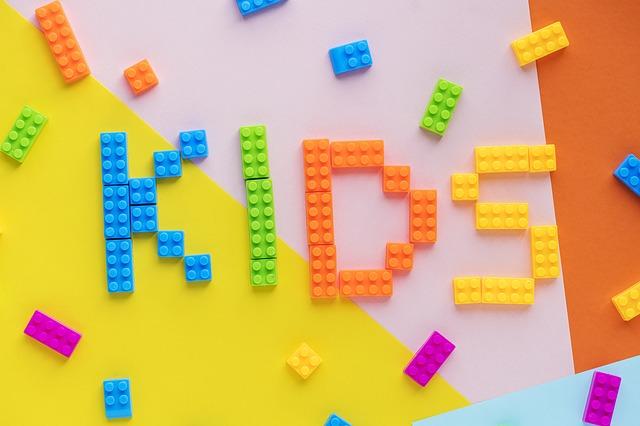 "nápis ""děti"" postavený z barevných lego kostek na barevném podkladu"