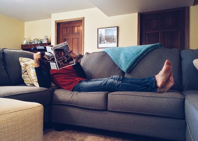 Muž ležící na pohovce a čtoucí noviny